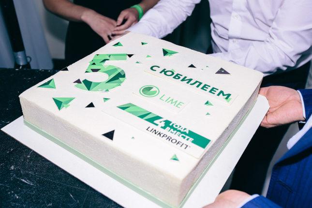 человек держит торт на пятилетии компании