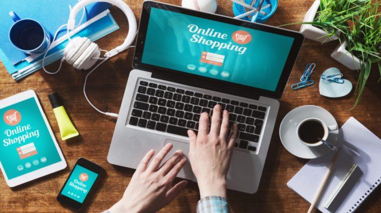 человек печатает на компьютере на экране которого написано online shopping