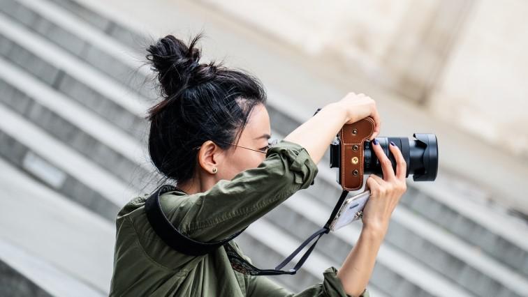 Девушка-фрилансер днем делает фото на фотоаппарат